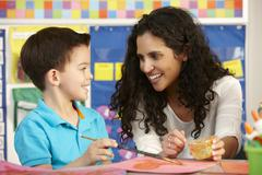 Elementary Age Pupil In Art Class With Teacher - stock photo