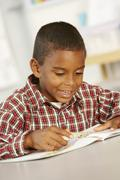 Elementary Age Schoolboy Reading Book In Class Stock Photos