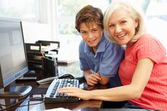 Mid age woman and grandson using computer - stock photo