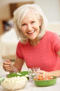 Mid age woman eating meal - stock photo