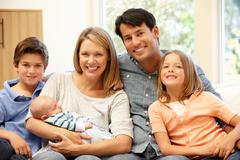 Family at home with new baby - stock photo