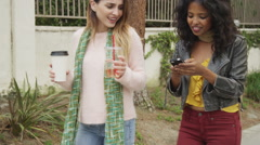 Happy friends walking together using smartphone Stock Footage