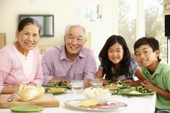 Asian family sharing meal at home Stock Photos