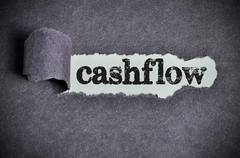 Cashflow word under torn black sugar paper Stock Photos