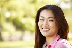 Head and shoulders portrait Asian woman outdoors - stock photo