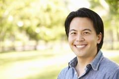 Head and shoulders portrait Asian man outdoors - stock photo