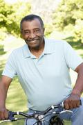 Senior African American Man Cycling In Park Stock Photos