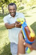 African American Grandfather And Grandson Playing With Water Pistols In Park - stock photo