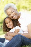 African American Grandmother And Granddaughter Relaxing In Park Stock Photos