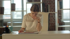 Businesswoman in the office at the table working on the touch pad tablet gadget Stock Footage