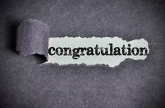 Stock Photo of congratulation  word under torn black sugar paper