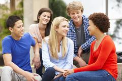 Multi racial student group sitting outdoors - stock photo