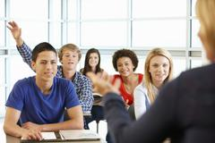 Multi racial teenage pupils in class one with hand up Stock Photos
