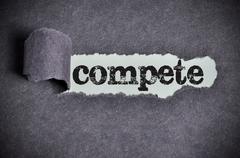 compete word under torn black sugar paper - stock photo