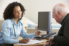 Young female Doctor with senior male patient Stock Photos