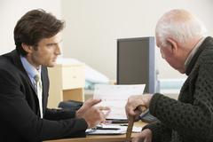 Doctor talking to senior male patient Stock Photos