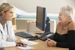 Doctor talking to senior woman patient - stock photo