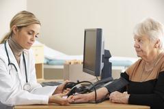 Doctor taking senior woman's blood pressure - stock photo