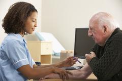 Nurse injecting senior male patient Stock Photos