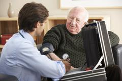 Doctor taking senior man's blood pressure at home Stock Photos