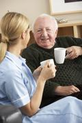 Nurse visiting senior man at home - stock photo