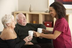Nurse visiting senior couple at home - stock photo
