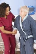 Nurse helping senior woman out of bed in hospital Stock Photos