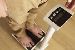 Man standing on digital scales cropped waist down Stock Photos
