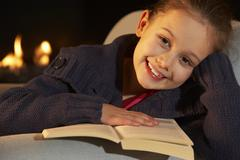 Portrait 7 year old girl reading by firelight Stock Photos