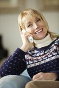 Senior woman talking on cordless phone at home Stock Photos