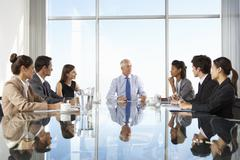 Group Of Business People Having Board Meeting Around Glass Table - stock photo