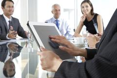 Close Up Of Businesswoman Using Tablet Computer During Board Meeting Around - stock photo