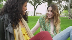 Close friends sitting outdoors telling each other stories Stock Footage