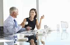 Two Business Colleagues Sitting Around Boardroom Table Having Informal - stock photo
