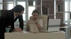 Portrait of a woman making a phone call while her colleague is working in a Stock Footage