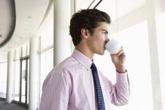 Young Businessman Standing In Corridor Of Modern Office Building Drinking Coffee Stock Photos