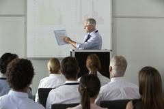 Middle Aged Businessman Delivering Presentation At Conference - stock photo
