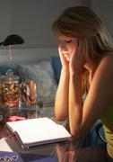 Unhappy Teenage Girl Looking At Diary In Bedroom At Night Stock Photos