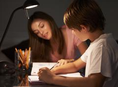 Teenage Sister Helping Younger Brother With Studies At Desk In Bedroom In - stock photo