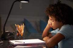 Unhappy Young Boy Studying At Desk In Bedroom In Evening - stock photo