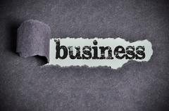 business word under torn black sugar paper - stock photo