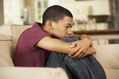 Unhappy Teenage Boy Sitting On Sofa At Home - stock photo