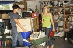 Two Teenagers Clearing Garage For Yard Sale Stock Photos