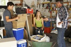Father Organising Two Teenagers Clearing Garage For Yard Sale - stock photo
