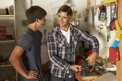 Father Teaching Son To Use Workbench In Garage Stock Photos