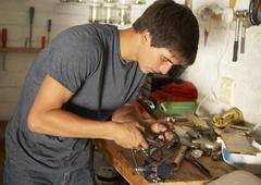 Teenage Boy Using Workbench In Garage Stock Photos