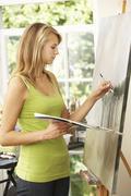 Teenage Girl Working On Painting In Studio - stock photo