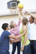 Teenage Family Playing Basketball Outside Garage Stock Photos