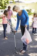 Family Picking Up Litter In Suburban Street - stock photo