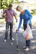 Couple Picking Up Litter In Suburban Street - stock photo